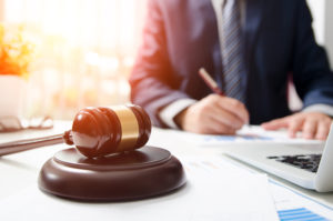 Florida Attorney Behind Gavel Assisting Client with Insurance Claim Paperwork
